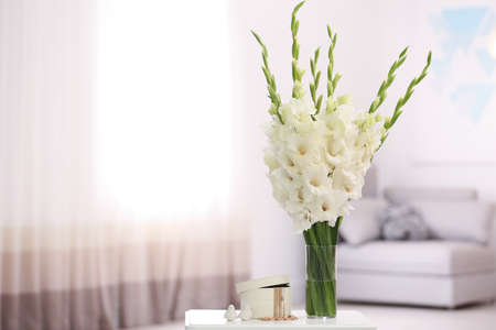 Vase with beautiful white gladiolus flowers and jewellery on wooden table in room, space for text Stock Photo