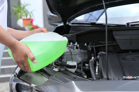 Man pouring liquid from plastic canister into car washer fluid reservoir, closeup