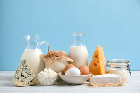 Different dairy products on white table against blue background Reklamní fotografie
