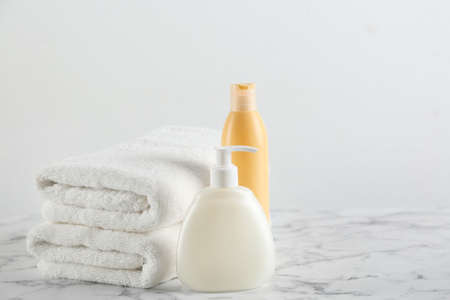 Fresh towels and toiletries on white marble table. Space for text Stock Photo