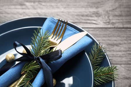 Christmas table setting on grey wooden background, closeup