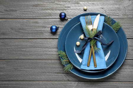 Christmas table setting on grey wooden background, flat lay. Space for text