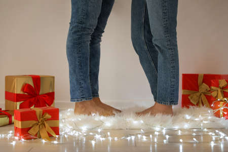 Young couple standing on rug near Christmas lights and gift boxes, closeup