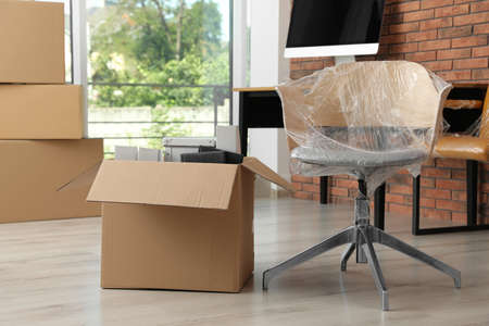 Cardboard box with belongings and packed chair in office. Moving service Stockfoto