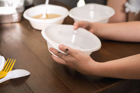Poor little child holding empty plate over wooden table in charity centre, closeup