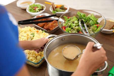 Volunteer serving food to poor people in charity centre, closeup