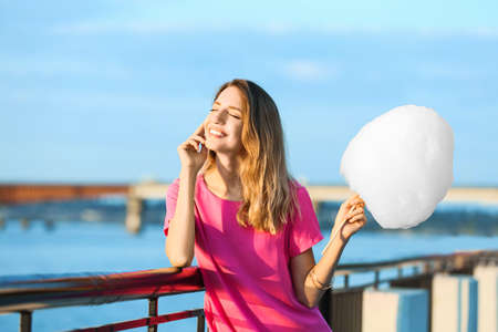 Happy young woman with cotton candy on waterfront Stock Photo
