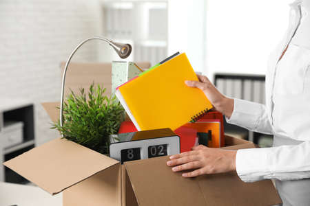 Young woman packing stuff in box at office, closeup Stockfoto
