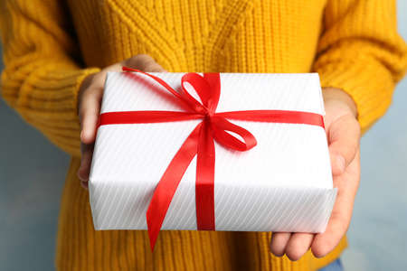 Young woman holding Christmas gift on blue background, closeup