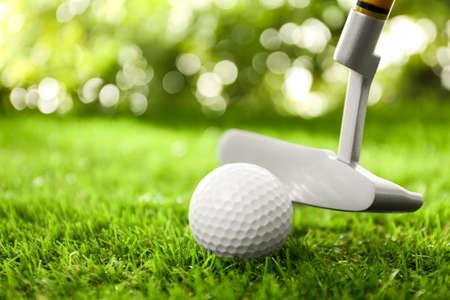 Hitting golf ball with club on green course 版權商用圖片
