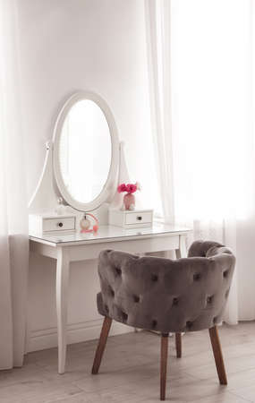 Elegant white dressing table and armchair in light room