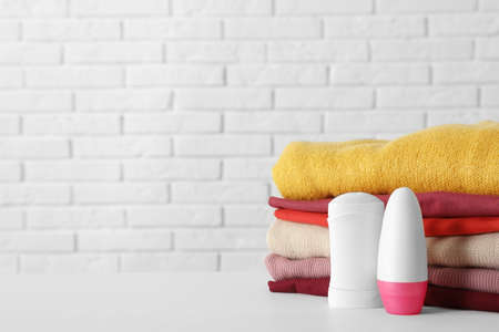 Deodorants near stack of clean clothes on white table. Space for text