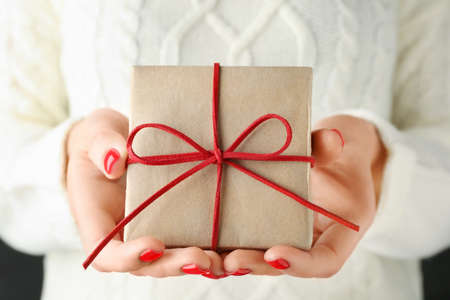 Woman holding beautiful Christmas gift with bow, closeup