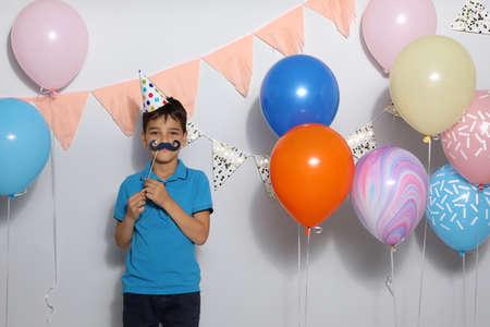 Happy boy near bright balloons at birthday party indoors
