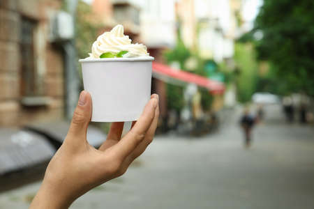 Woman holding cup with tasty frozen yogurt outdoors, closeup. Space for text Banque d'images - 131631562