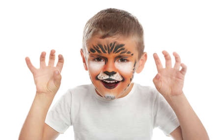 Cute little boy with face painting on white background