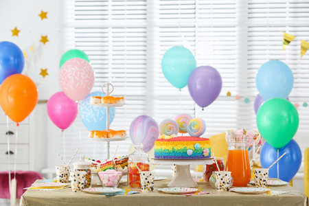Bright birthday cake and other treats on table in decorated room Reklamní fotografie