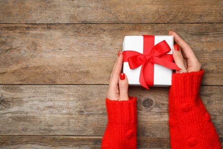 Young woman holding Christmas gift on wooden background, top view. Space for text Stock Photo