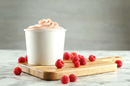Cup with tasty frozen yogurt and raspberries on marble table. Space for text