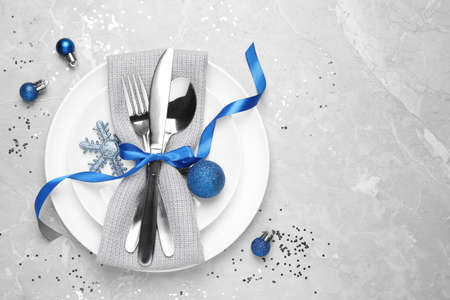Beautiful Christmas table setting on grey background, flat lay. Space for text