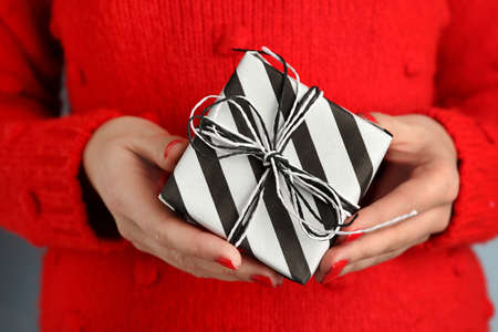 Young woman holding gift, closeup view Stock Photo