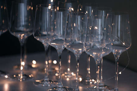 Empty clean glasses and fairy lights on table Stok Fotoğraf