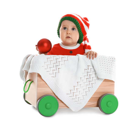 Cute little baby wearing elf hat in wooden cart on white background. First Christmas Stock Photo