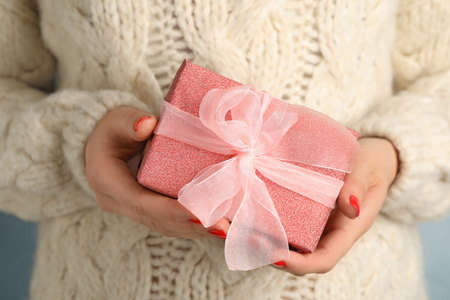 Young woman holding gift, closeup view