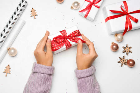 Young woman holding Christmas gift on white background, flat lay Stock Photo - 130804766