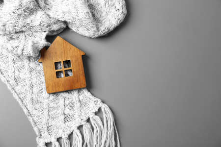 Wooden house model and scarf on grey background, top view with space for text. Heating efficiency