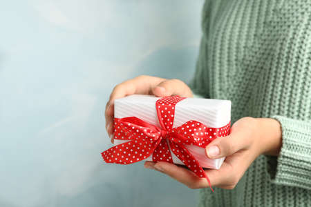 Woman holding beautiful Christmas gift on light blue background, closeup Stock Photo - 130805135