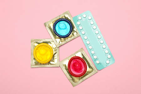 Condoms and birth control pills on pink background, top view. Safe sex Stock Photo