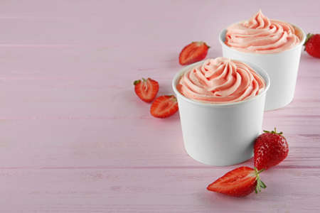 Cups with tasty frozen yogurt and strawberries on pink wooden table. Space for text Banque d'images - 131632011