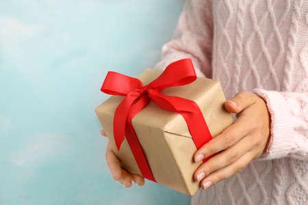 Woman holding beautiful Christmas gift on light blue background, closeup Stock Photo
