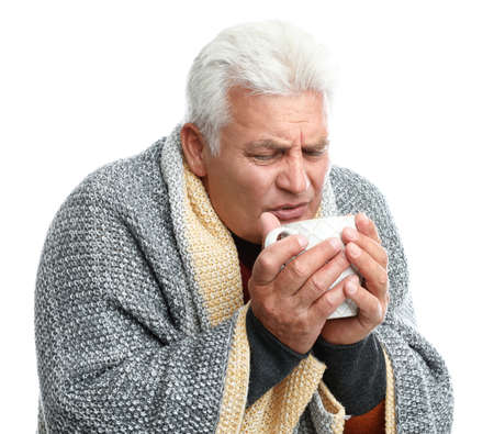 Mature man with cup of hot beverage suffering from cold on white background