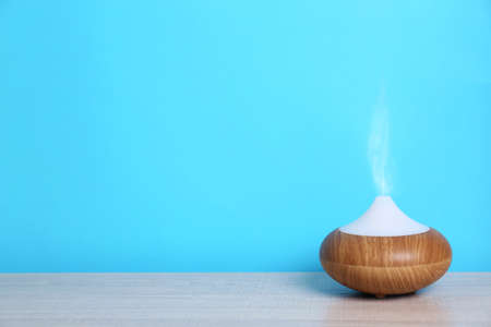 Essential oils diffuser on table near blue wall. Space for text 写真素材