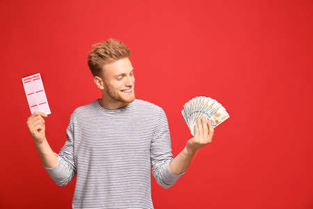Portrait of happy young man with money fan and lottery ticket on red background Фото со стока