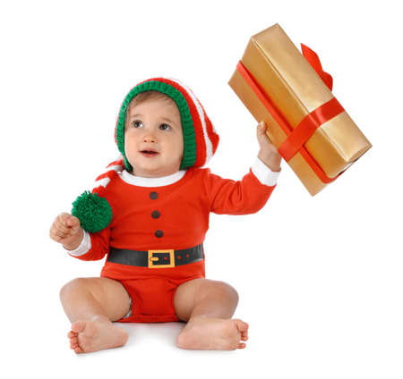 Festively dressed baby with gift box on white background. Christmas celebration