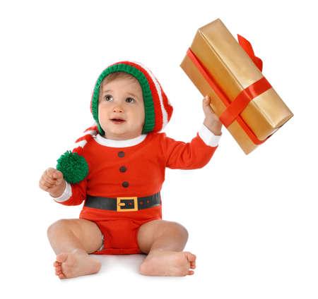 Festively dressed baby with gift box on white background. Christmas celebration 스톡 콘텐츠 - 132349293