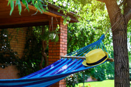 Comfortable blue hammock with hat outdoors on sunny day