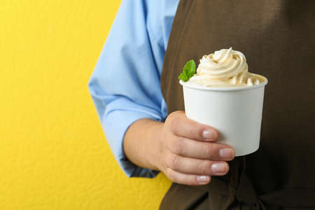 Woman holding cup with tasty frozen yogurt on yellow background, closeup Banque d'images - 131670299
