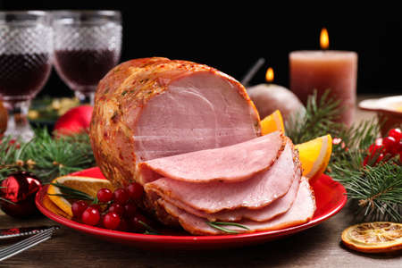 Plate with delicious ham served on wooden table. Christmas dinner
