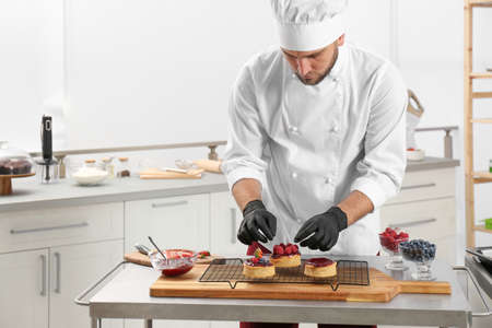 Male pastry chef preparing desserts at table in kitchen Banque d'images
