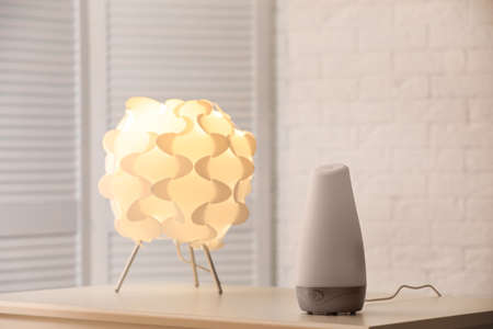 Modern essential oil diffuser on table indoors