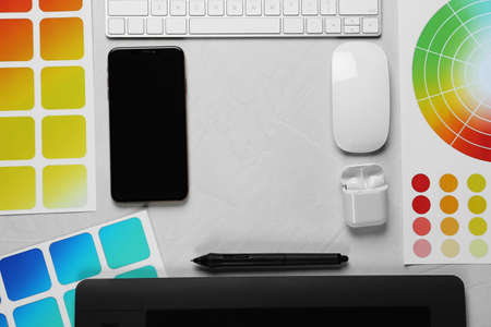 Flat lay composition with digital devices and color palettes on white background, space for text. Graphic designers workplace Stock Photo