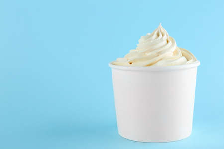 Cup with tasty frozen yogurt on blue background. Space for text Banque d'images - 131555112