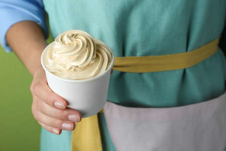Woman holding cup with tasty frozen yogurt on green background, closeup Banque d'images - 131555702