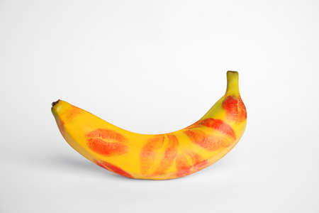Fresh banana with red lipstick marks on white background. Oral sex concept