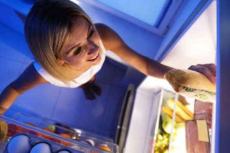 Woman taking sandwich out of refrigerator in kitchen at night, high angle view