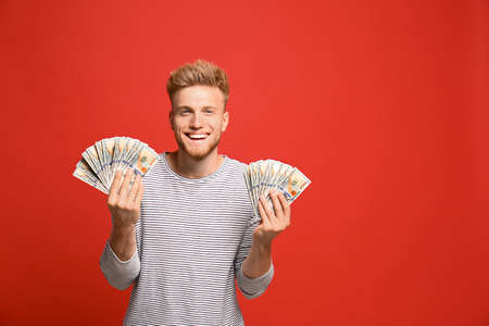 Portrait of happy lottery winner with money on red background